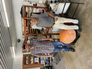 two men standing by giant pumpkin